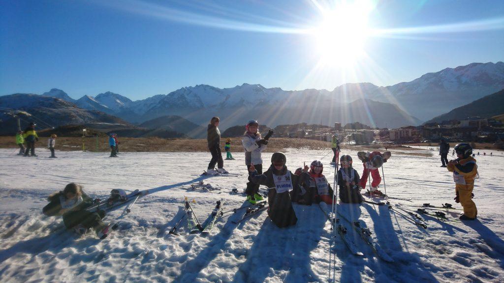 enfants assis au goûter sur les pistes